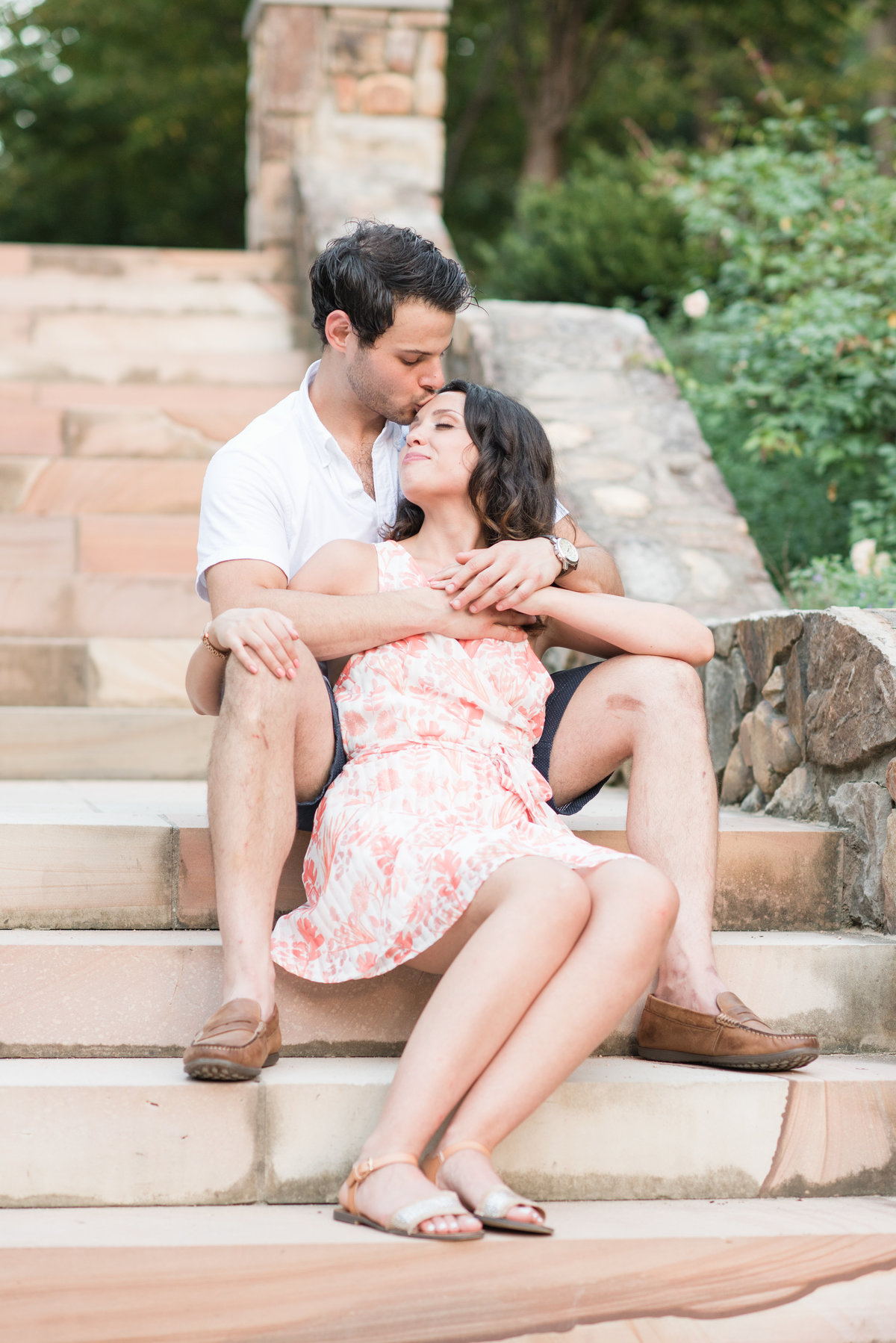 an engagement session at Sarah P Duke Gardens with a bride sitting on the marbled steps snuggled into her fiance getting kissed on the forehead in front of a rose garden in Durham