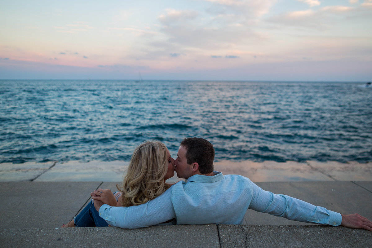 guy and girl kissing while overlooking lake michigan at alder planetarium