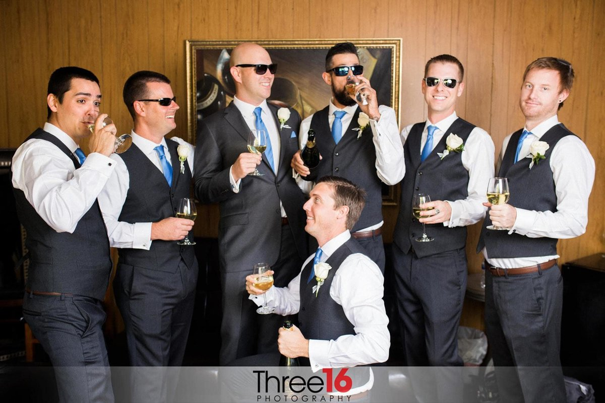 Groom and his Groomsmen acting up with drinks before the wedding