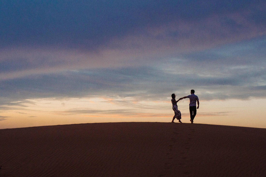 Couple walks along the sand dunes for their Glamis engagement session.