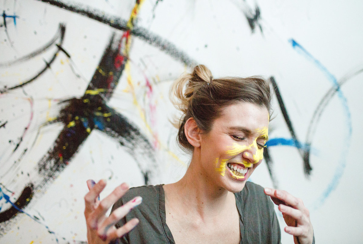 anna canfield laughs after she paints her face with a paintbrush of eyllow paint against her artwork background