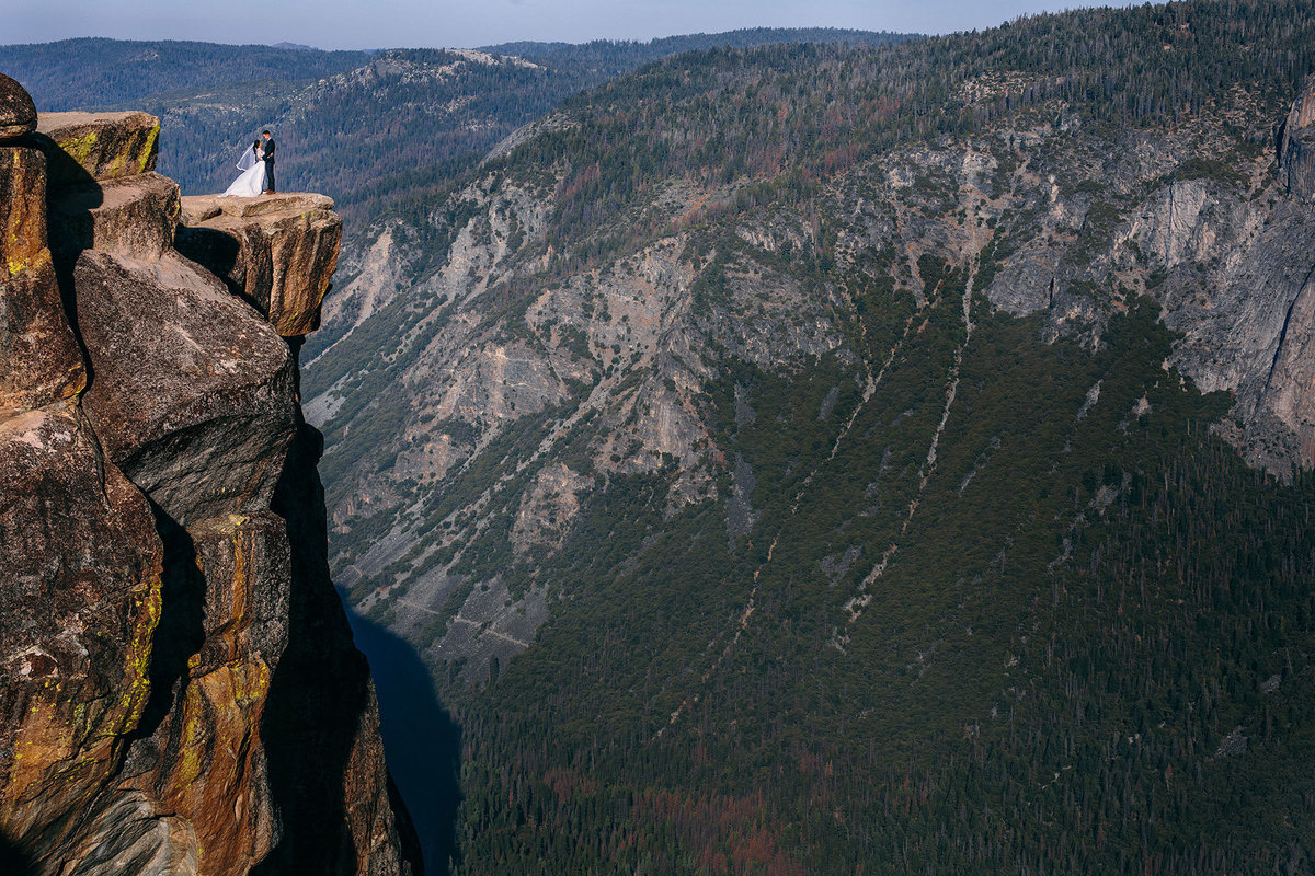 Bride & groom daringly pose on Taft Point in Yosemite after their Taft Point Yosemite wedding ceremony.
