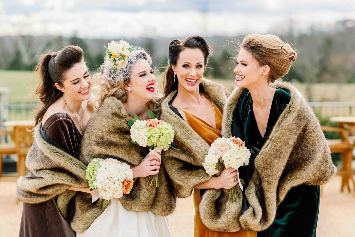 bride and bridesmaids laugh at eachother at the farm in virginia
