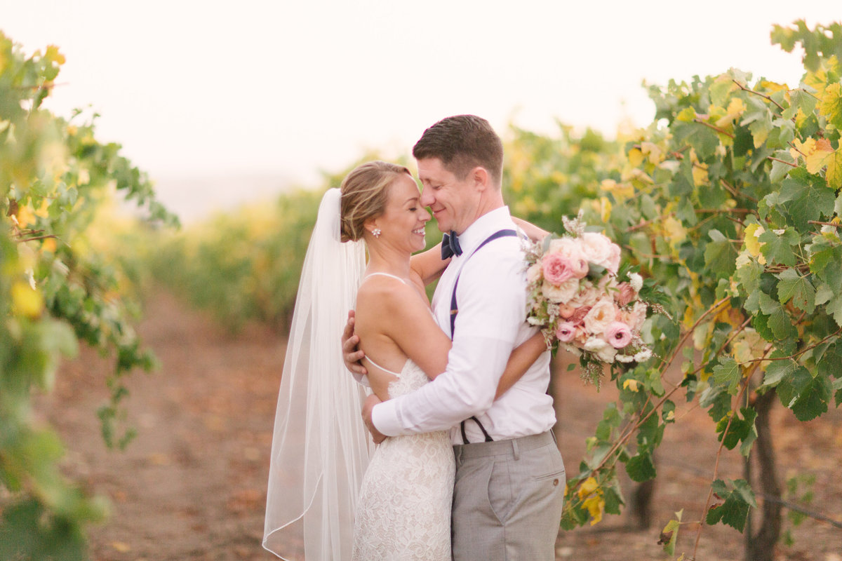 Groom pulls bride in close after Firestone Vineyard wedding