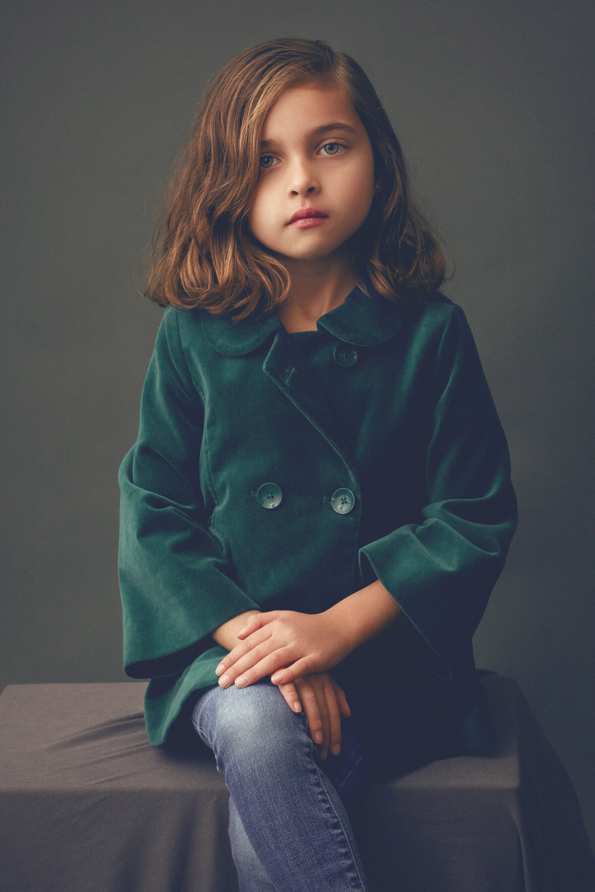 Child portrait of a young girl sitting with leg crossed, looking at camera center.