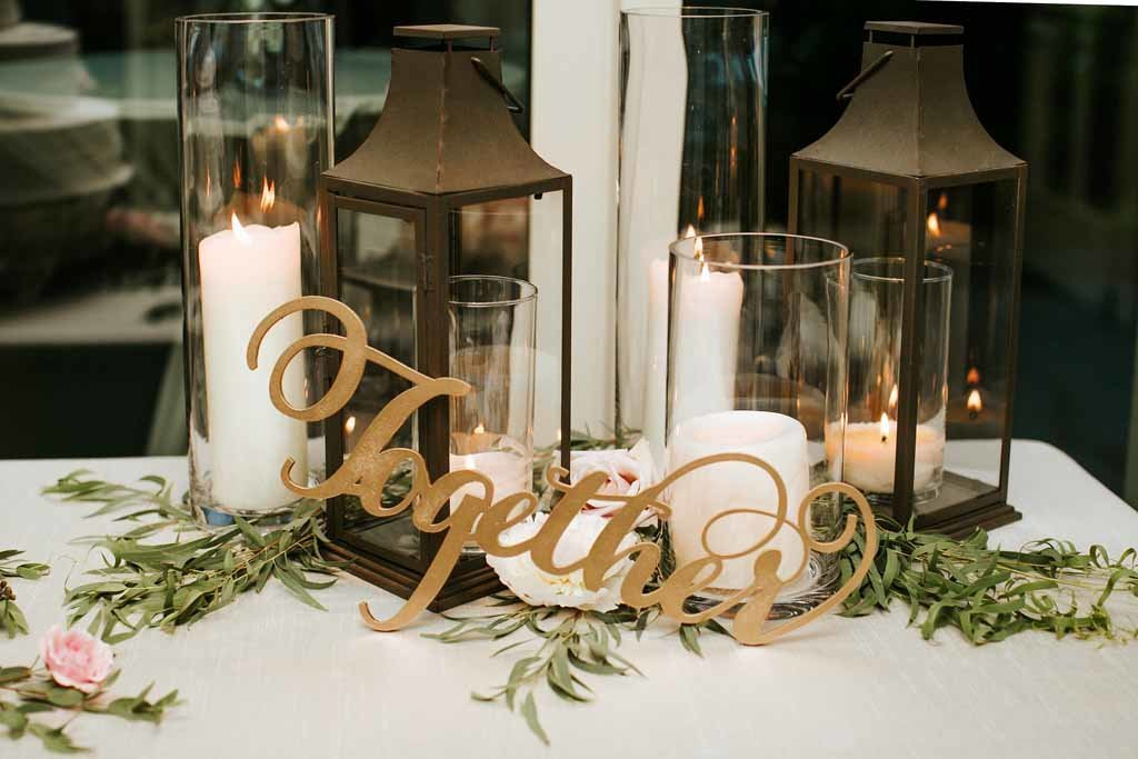 Beautiful details of hurricane candles and lanterns at this summer tent wedding