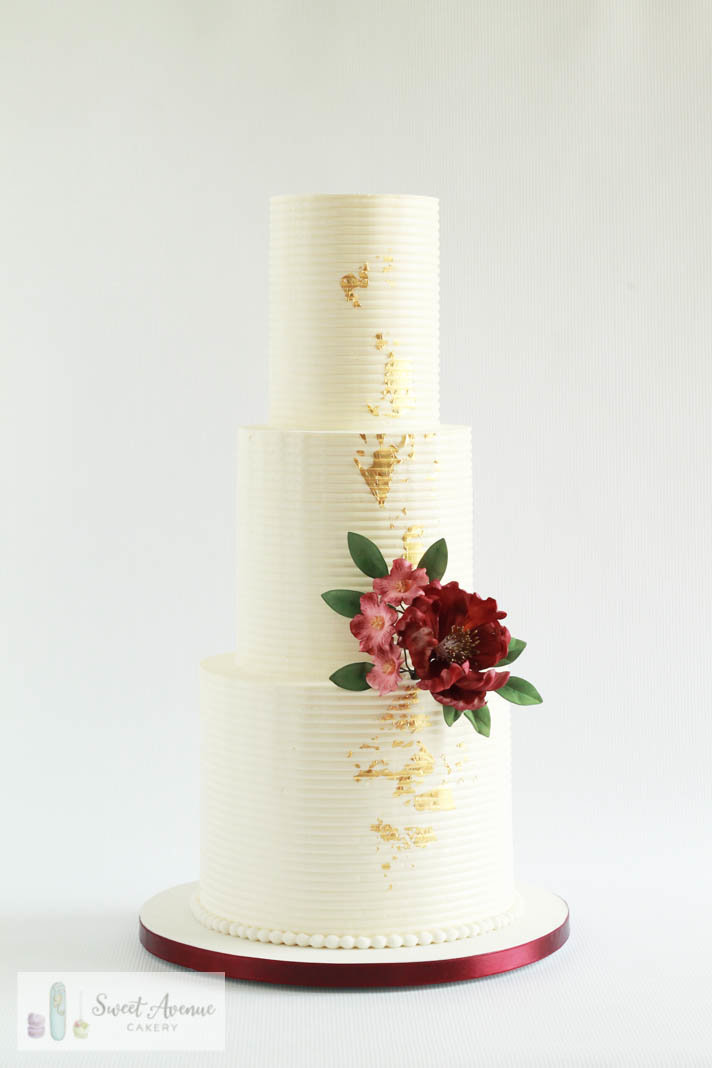 striped buttercream wedding cake with gold foil and burgundy flowers