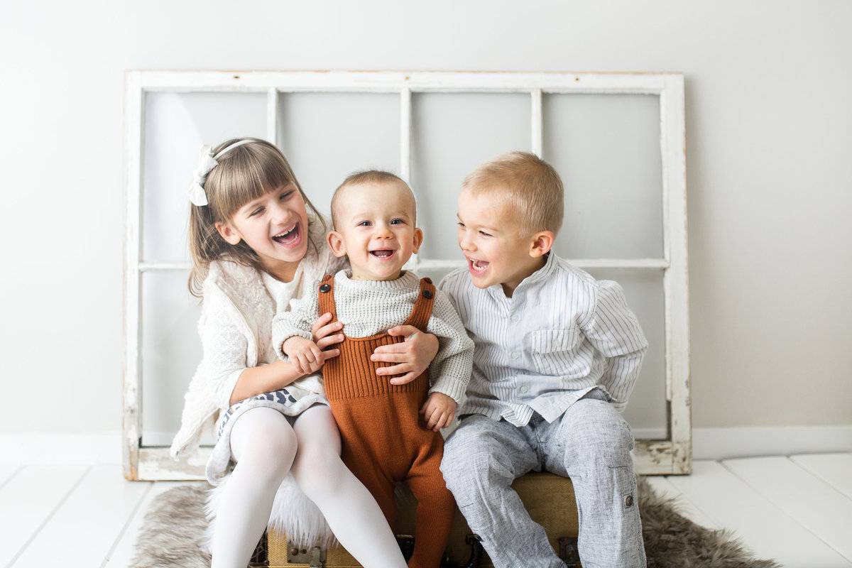3 young children cuddled together smiling in studio {Oakville Child Photographer}