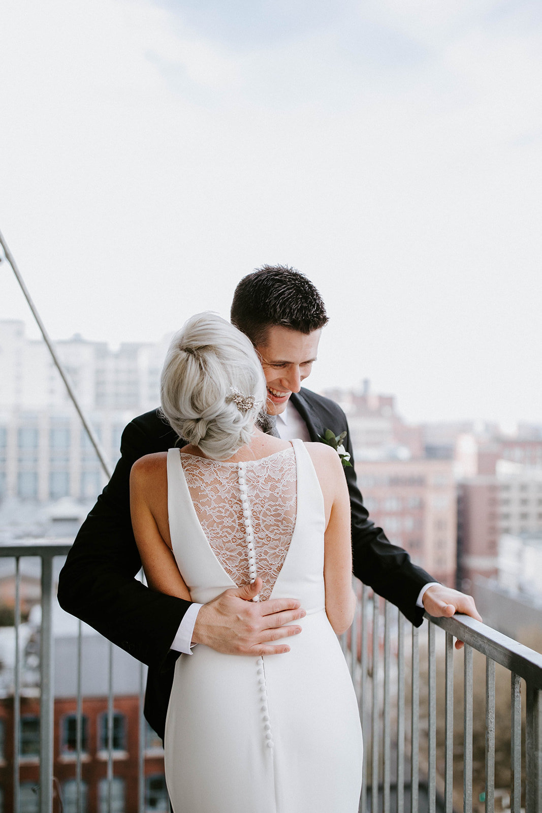 A bride and groom embrace on a balcony.