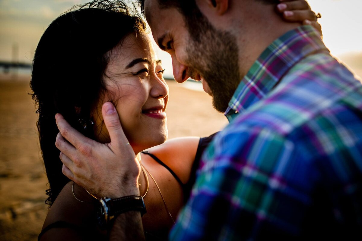 A couple embraces during a North Avenue beach engagement session.