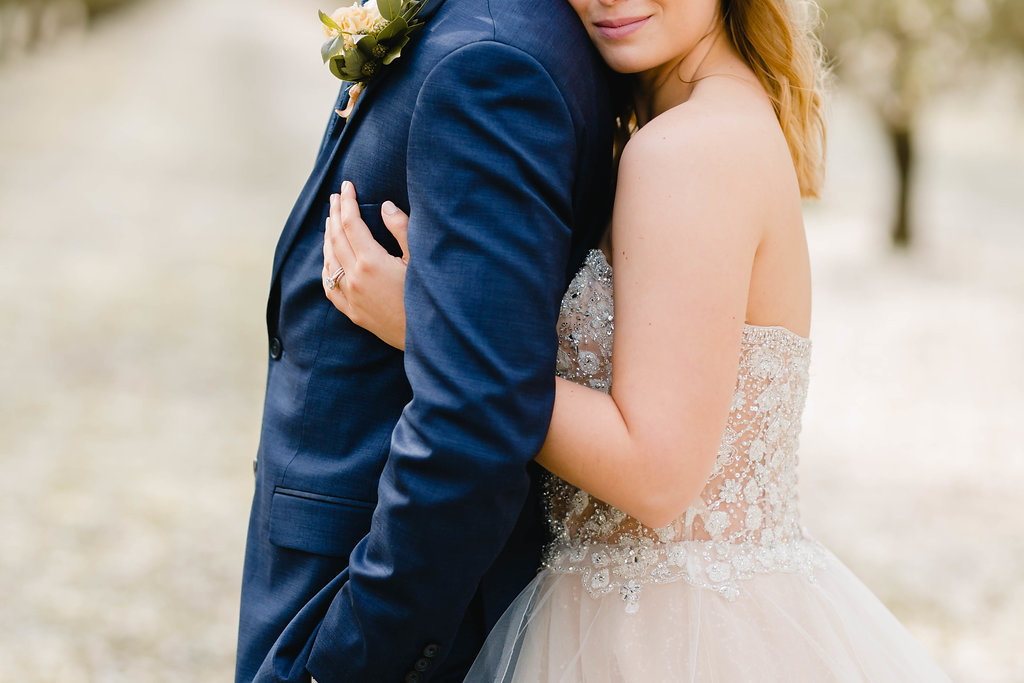 close up of a bride and groom's arms embracing in an orchard