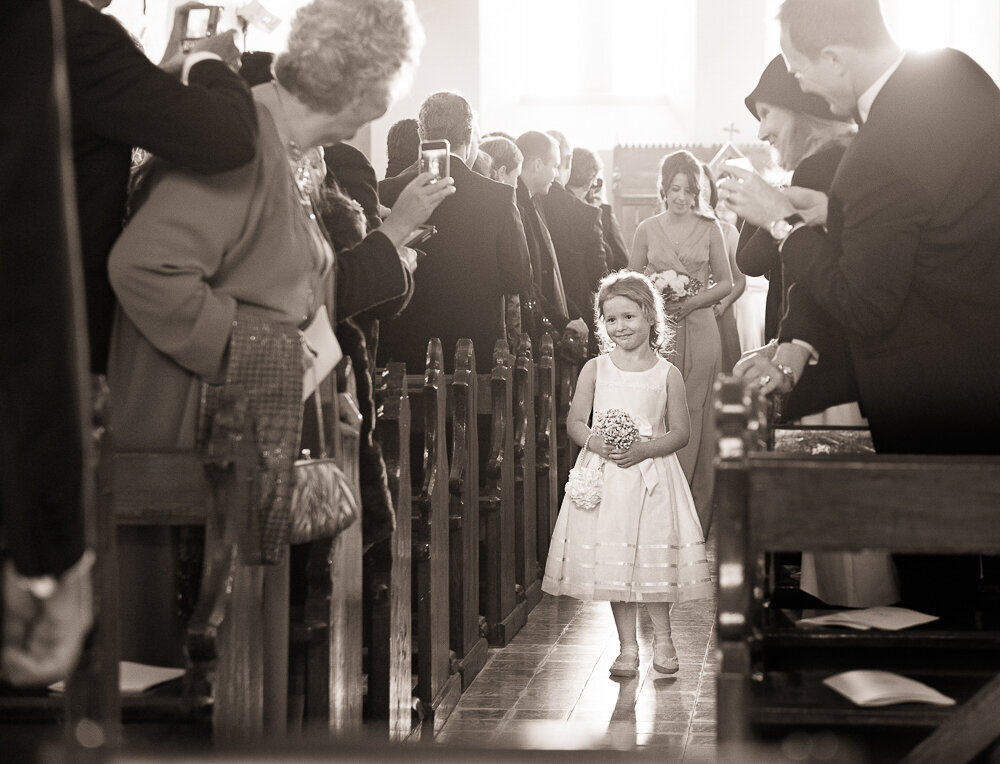 flower girl wearing short dress walking up the aisle of the church while wedding guests look on