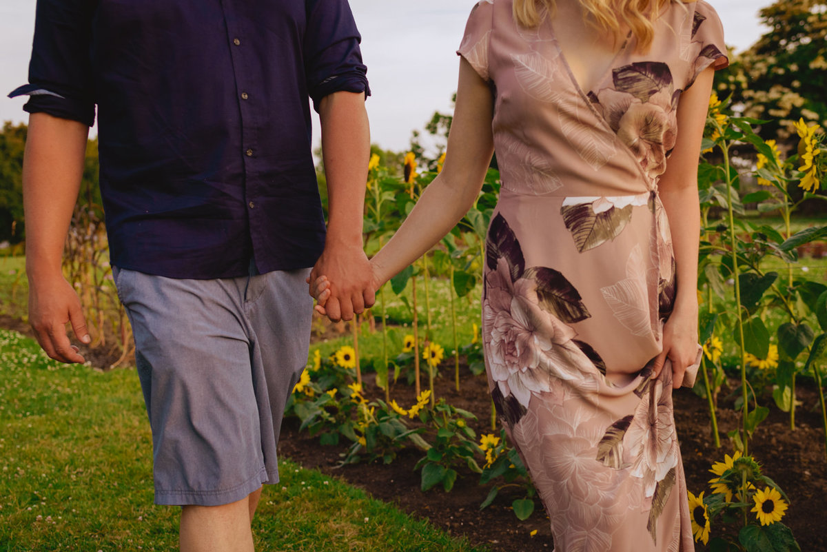 engaged couple holding hands walking through field of sunflowers