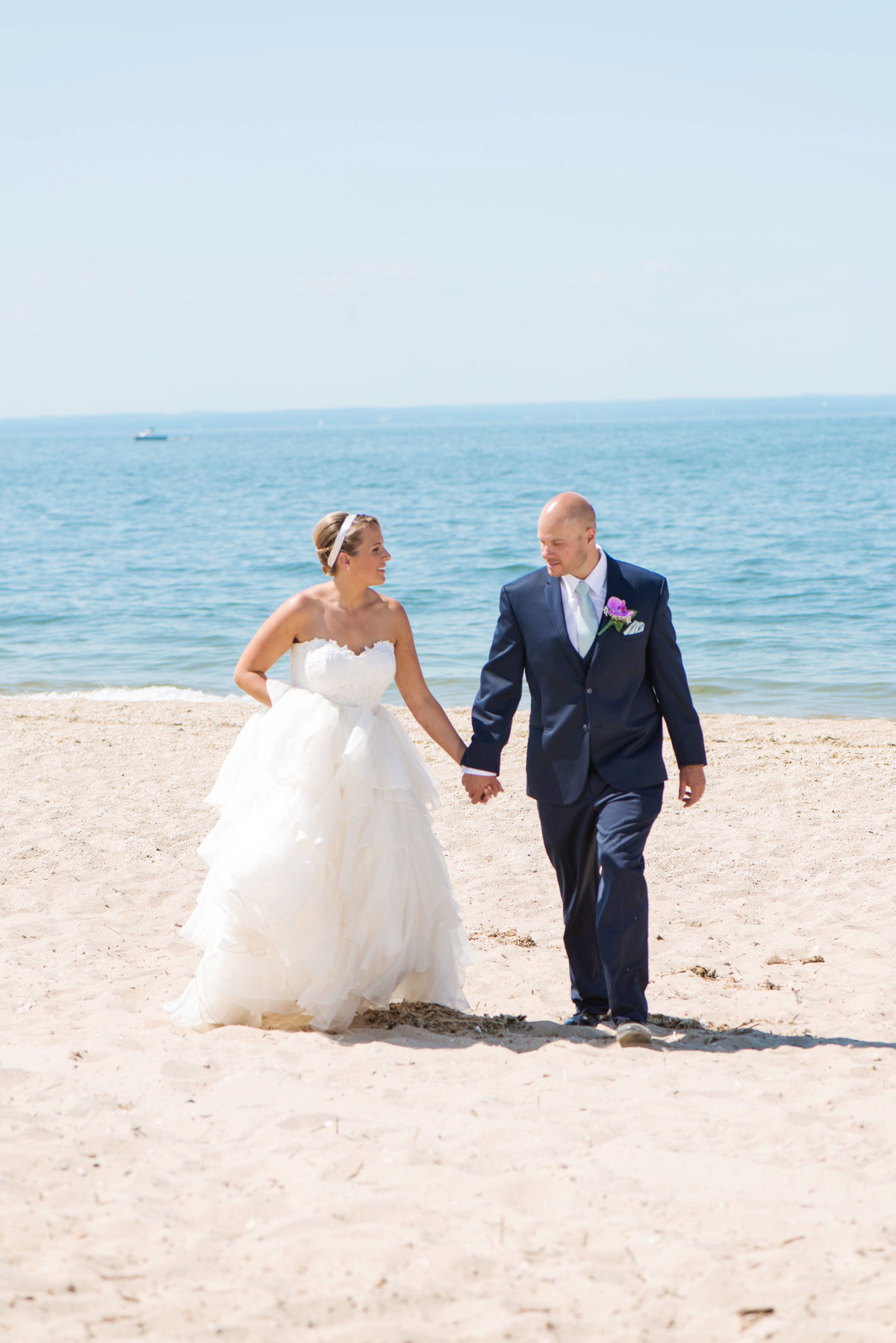 photo of bride and groom walking down the beach from wedding at Pavilion at Sunken Meadow