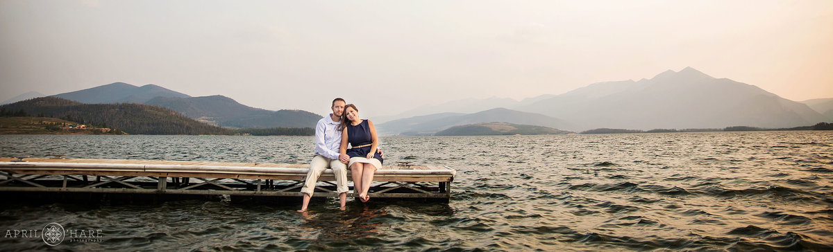 Cute couple sits on the dock at Lake Dillon at Sunset Engagement Session in Summit County Colorado