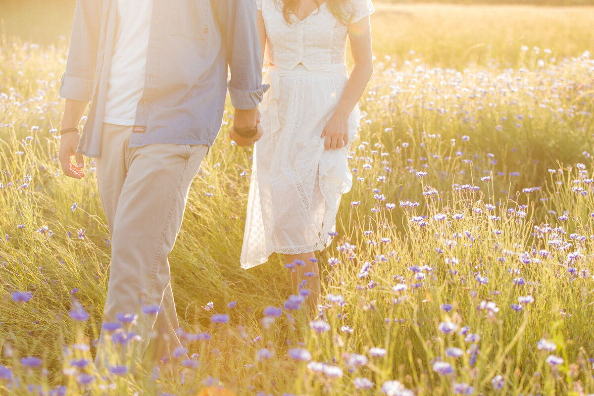 couple walking through wildflower field at sunset during golden hour glow