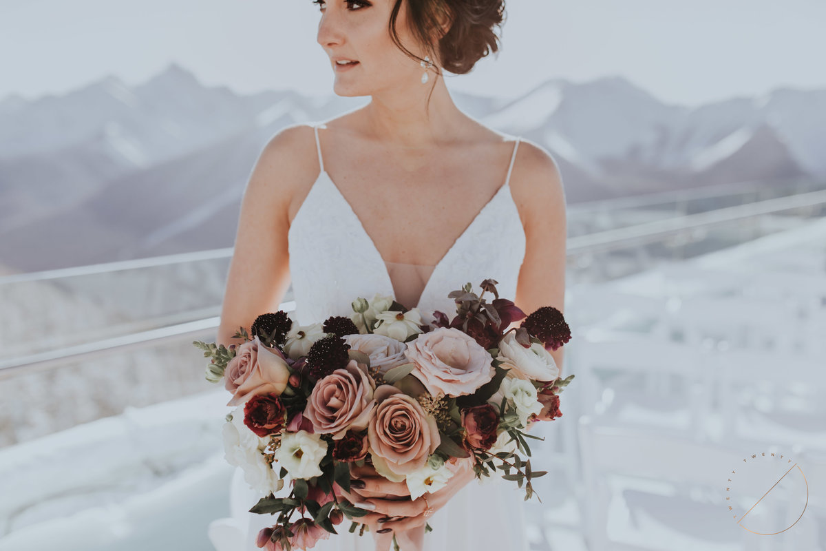 beautiful photo taken at the top of Sulphur Mountain on the terrace of Banff Gondola, one of the best places to host a wedding in the Rocky Mountains, floral bouquet made by Flowers by Janie and photo by Twenty Twenty Photography