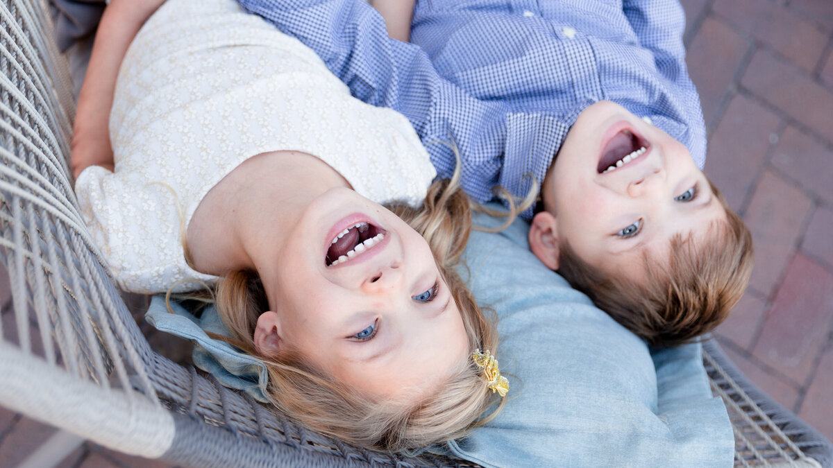 two children laughing upside down