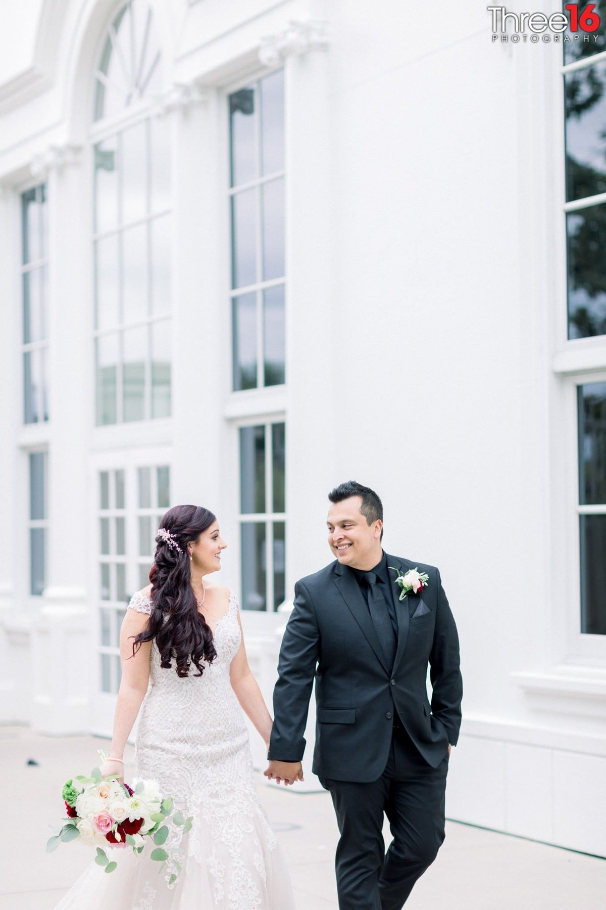 Bride and Groom smile at each other while holding hands