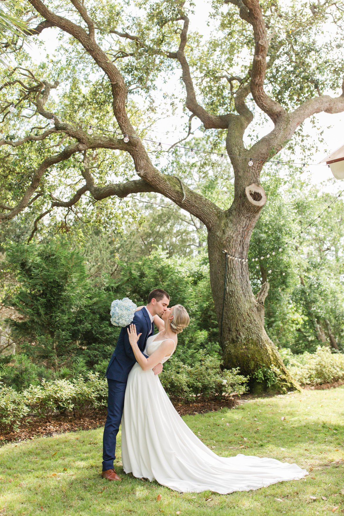 groom dipping bride in front of oak tree at tybee wedding chapel