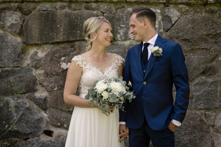 Bride with lace dress, loose up do and white and green wedding bouquet and groom in navy suit and white rose lapel flower stand in front of stone wall at Krusenberg Herrgård wedding and smile at each other