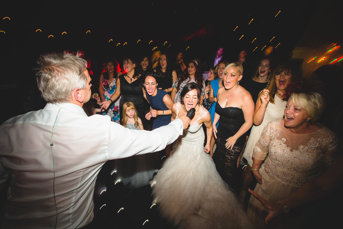 bride on dancefloor singing