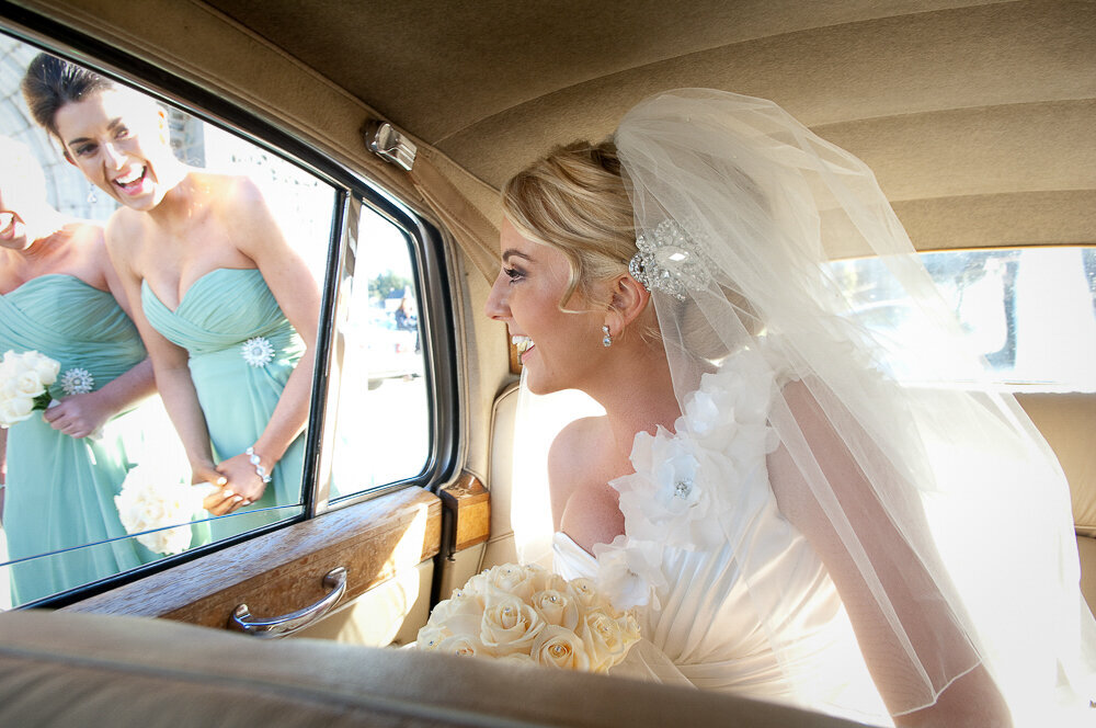 bride with blonde hair wearing a one strap, mermaid style wedding dress looking out the window of a vintage car at her bridesmaids wearing sage green, column style dresses