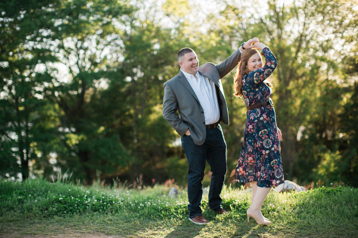 Wedding Photographer, couple dancing together in the grass and sun
