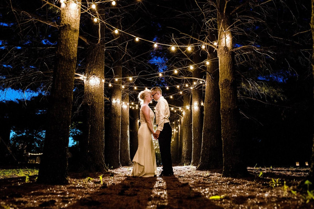 A couple holds hands at night during their Oak Hill Farm wedding.