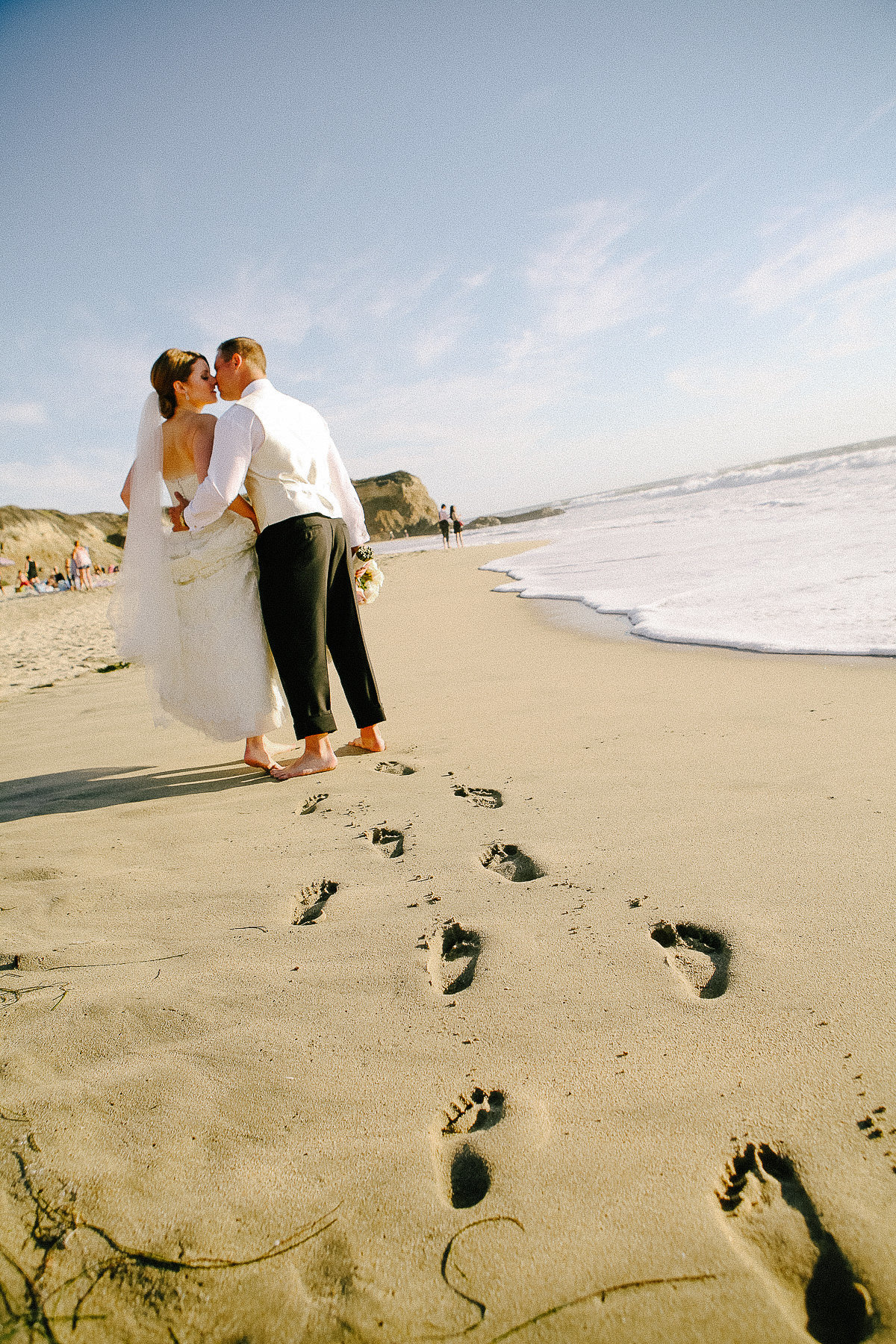 A bride and groom walk along the beach at their wedding at the Ritz-Carlton in Half Moon Bay.