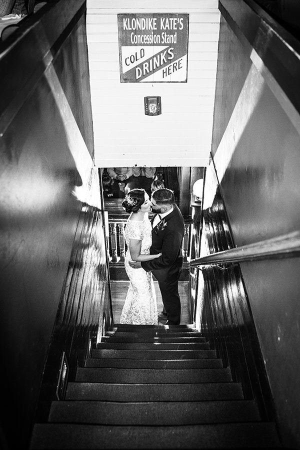 A bride and groom kiss at the bottom of a stairway, light is popped behind them for dramatic effect
