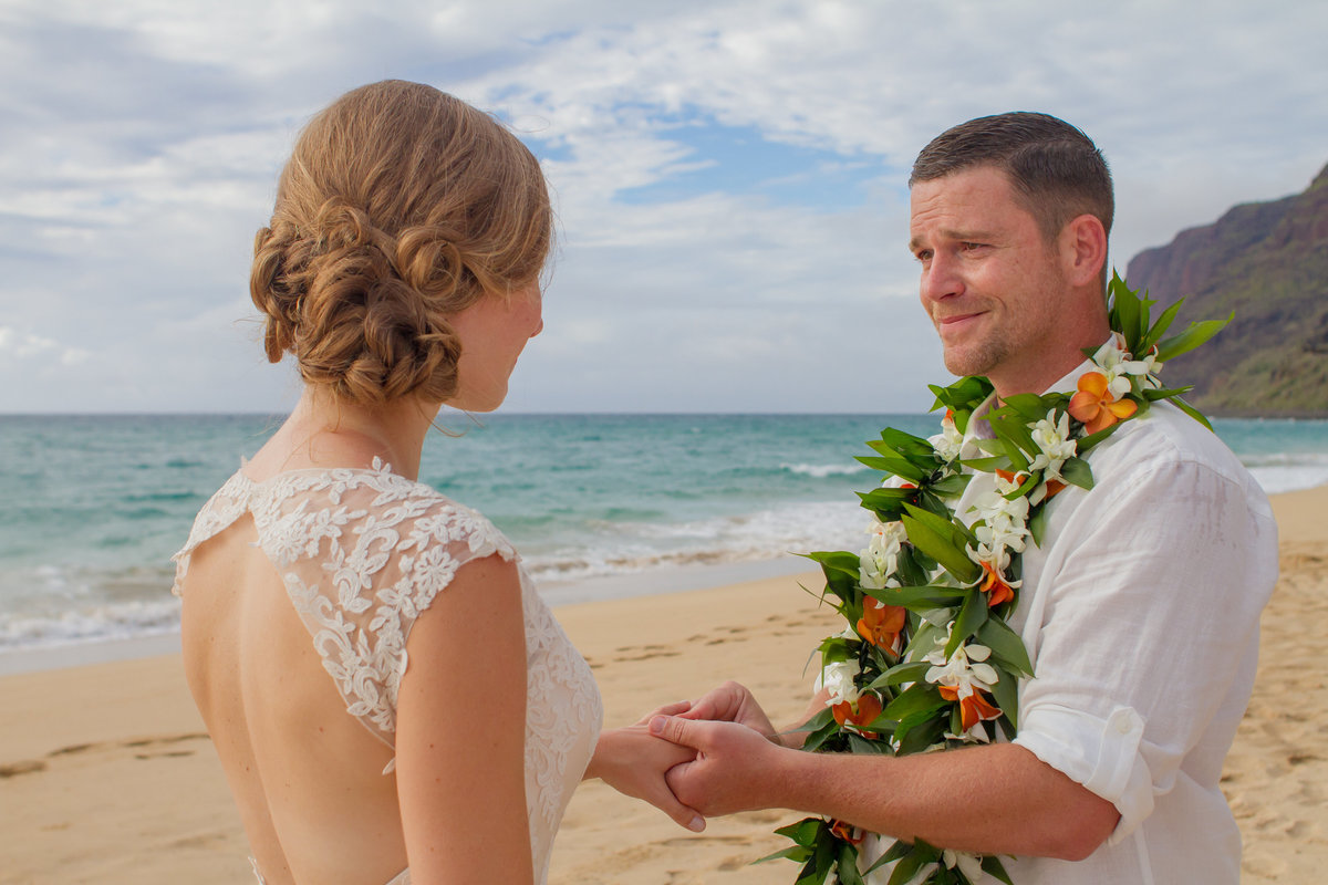 Groom wearing ti and orchid lei gives bride her wedding ring during Kauai wedding ceremony.