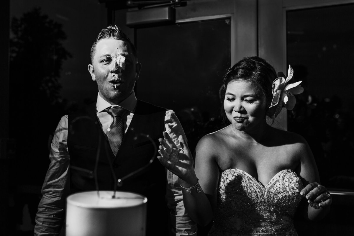A bride shoves cake in the grooms confused face during the reception
