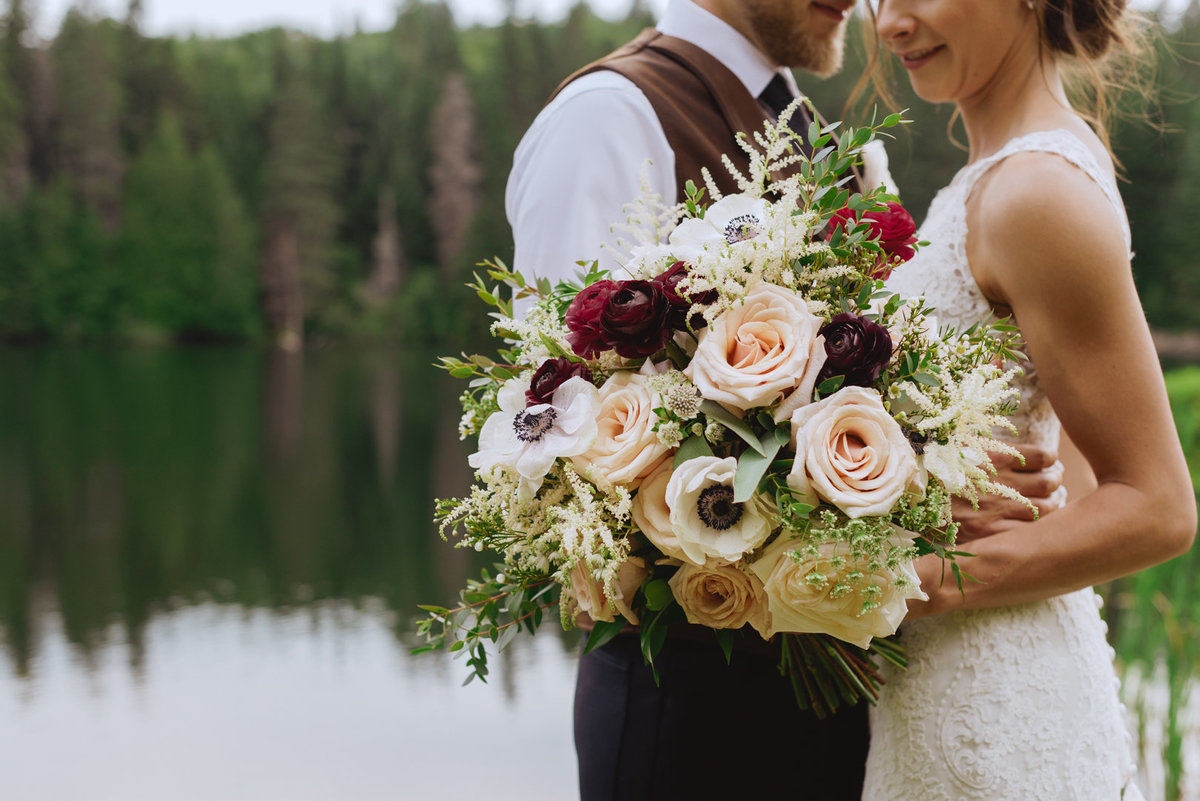 bridal bouquet by the water with evergreen trees
