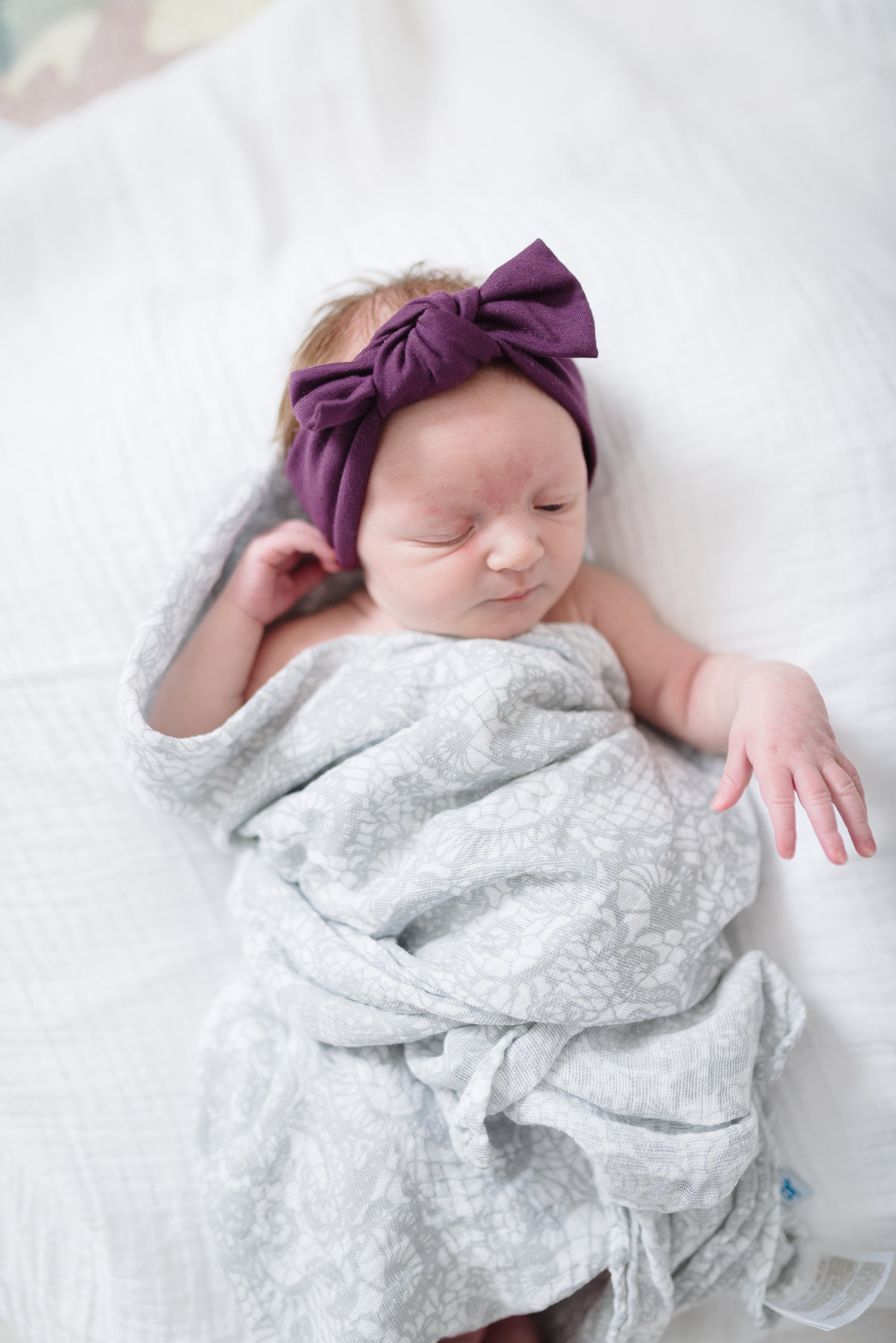 Newborn Baby Girl is wearing a purple headwrap and is wrapped in a gray swaddle blanket