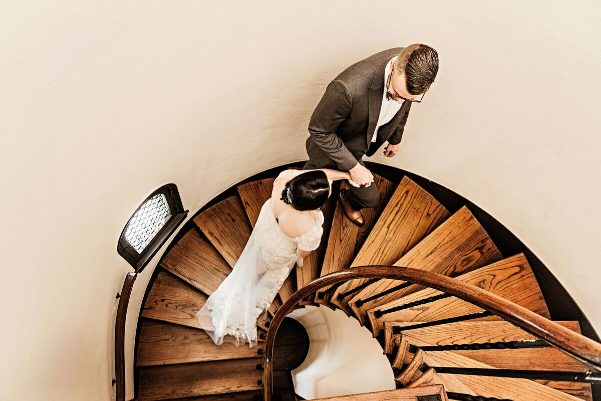 An image of the bride and groom from above, holding hands, climbing a circular wooden stairway in a tower at their wedding venue, as they gaze at one another by Garry & Stacy Photography Co - Tampa Florida wedding photographers