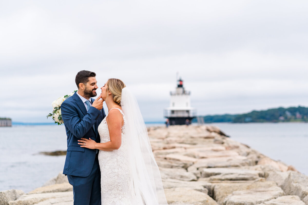 Couple reading their vows out of vow books on the rocky coast of  Portland, Maine during their elopement-Destination Elopement Photographer