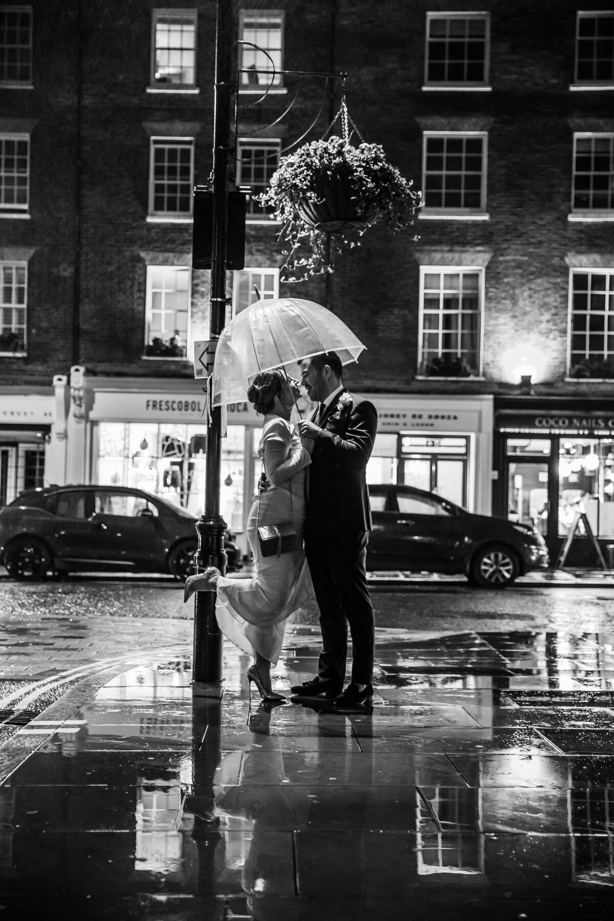 Bride and Groom kissing in the rain outside chiltern firehouse