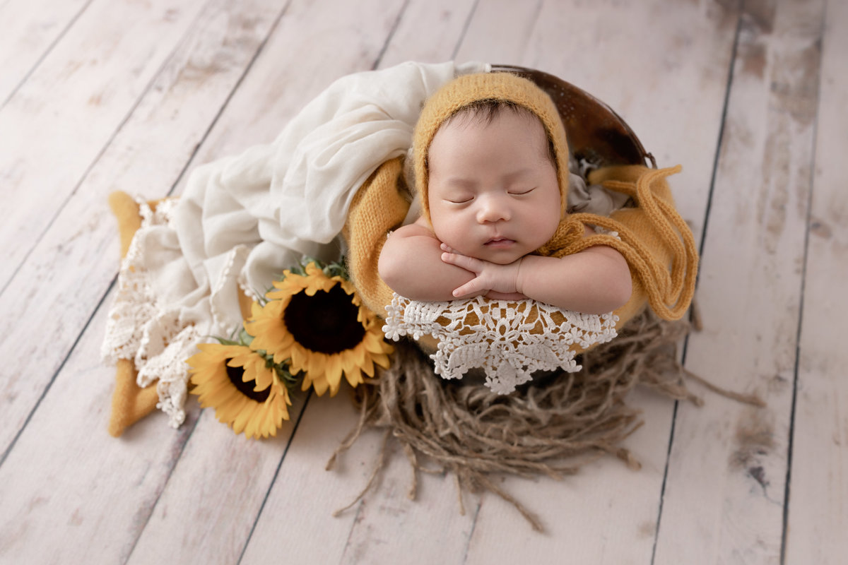 Baby in a bucket with sunflowers in yellow