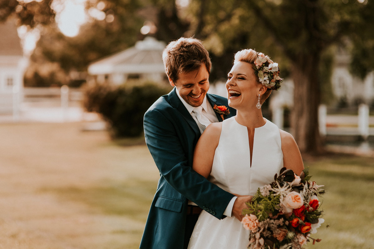 A bride and groom laugh as they have the time of their life on a gorgeous day in the fall