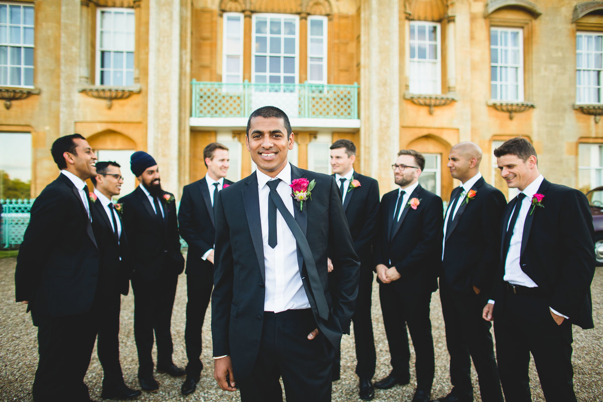 groom in black suit and black tie with friends at sezincote house