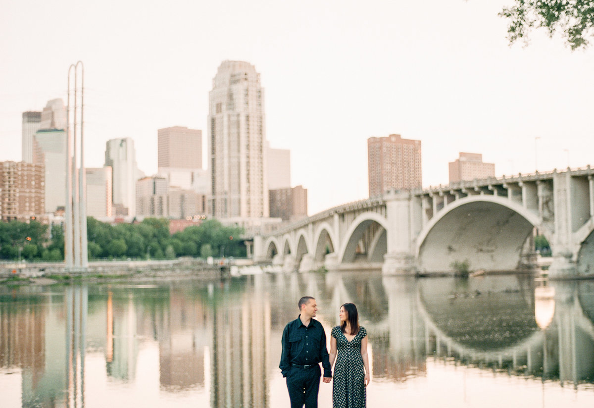 fiances hold hands over mississippi river with minneapolis skyline in the background