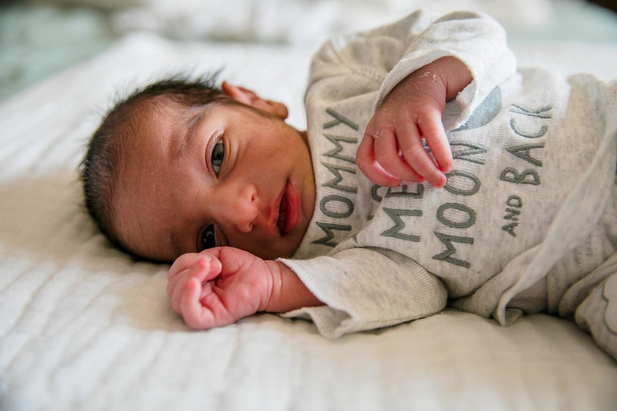 newborn baby boy laying in bed with eyes open and looking at the camera