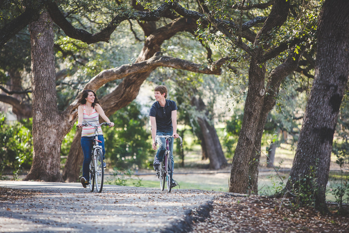 Man and woman riding their bike on their engagement session at Denman Estate Park.