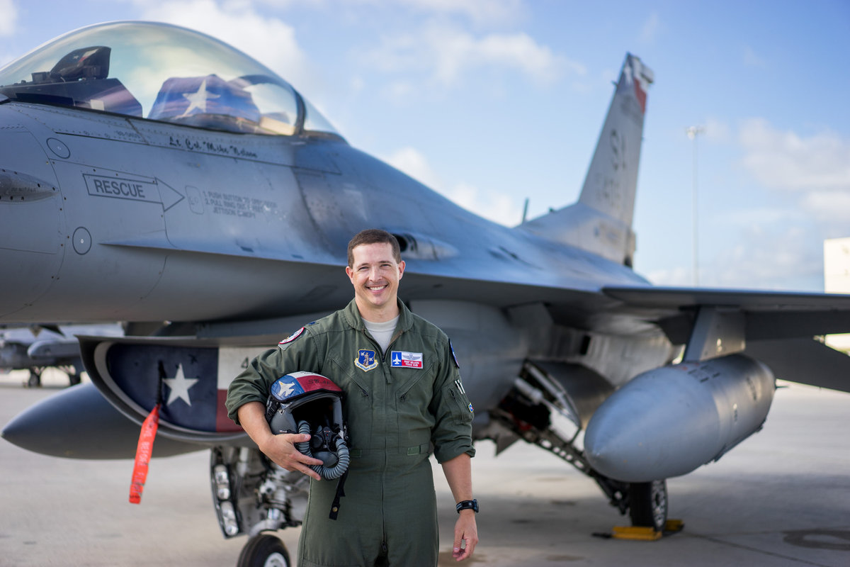 Air Force pilot standing in front of his jet that has a Texas flag painted on it on a military base in San Antonio.