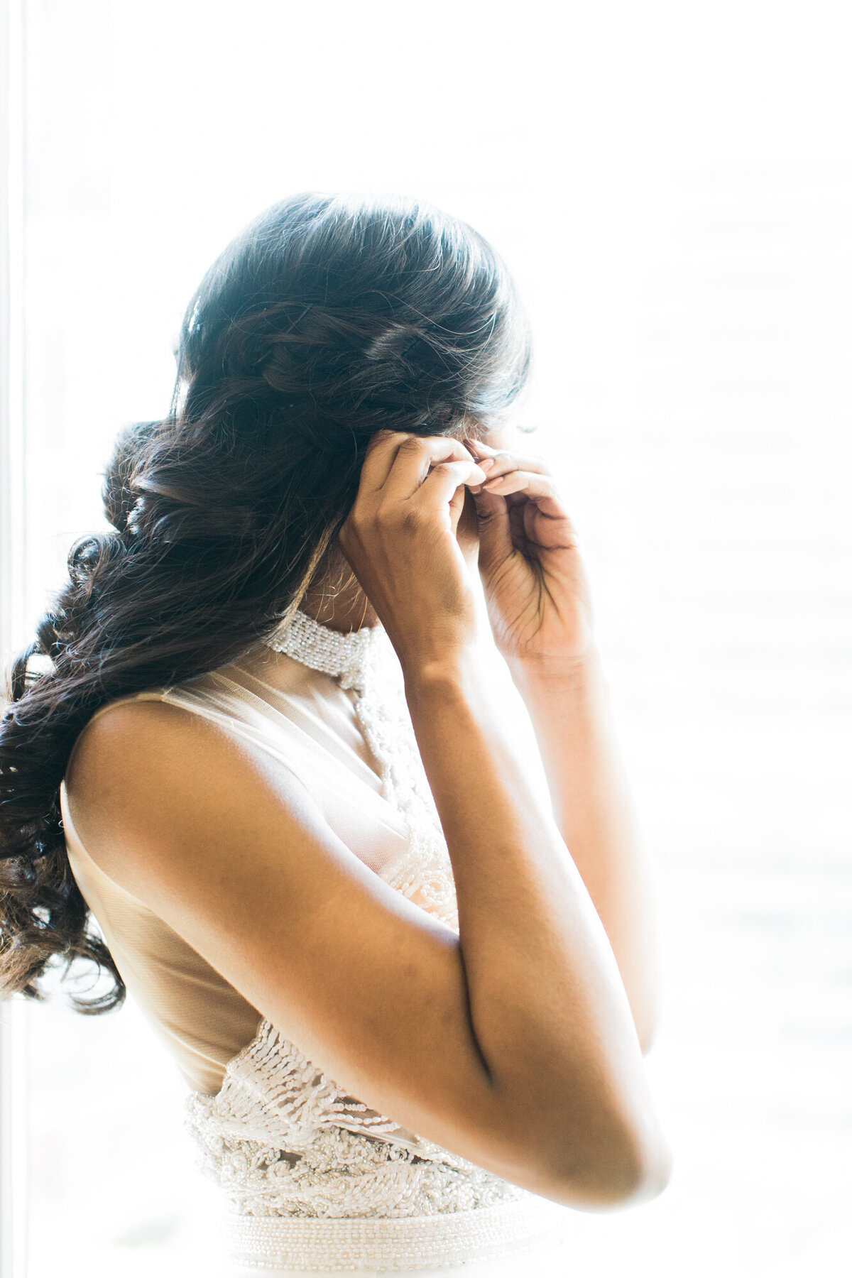 Bride standing in window putting on earrings