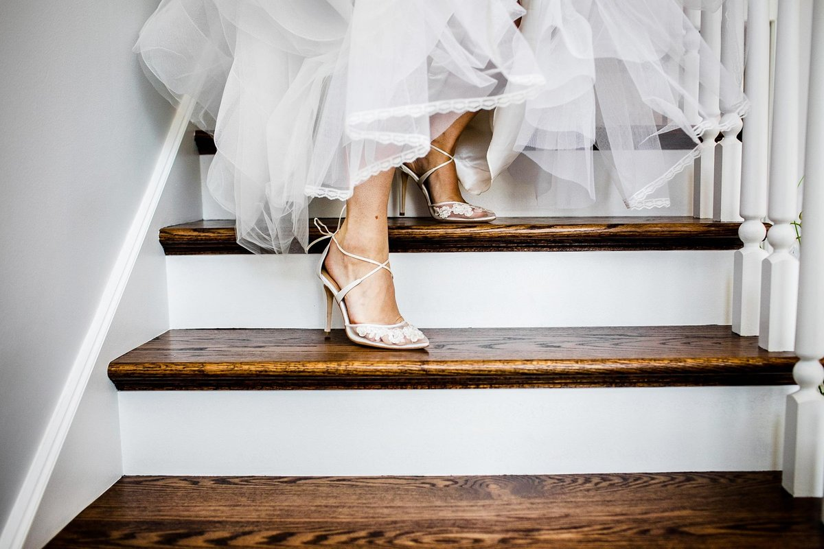 A bride walks down the stairs before her Glen Club wedding.