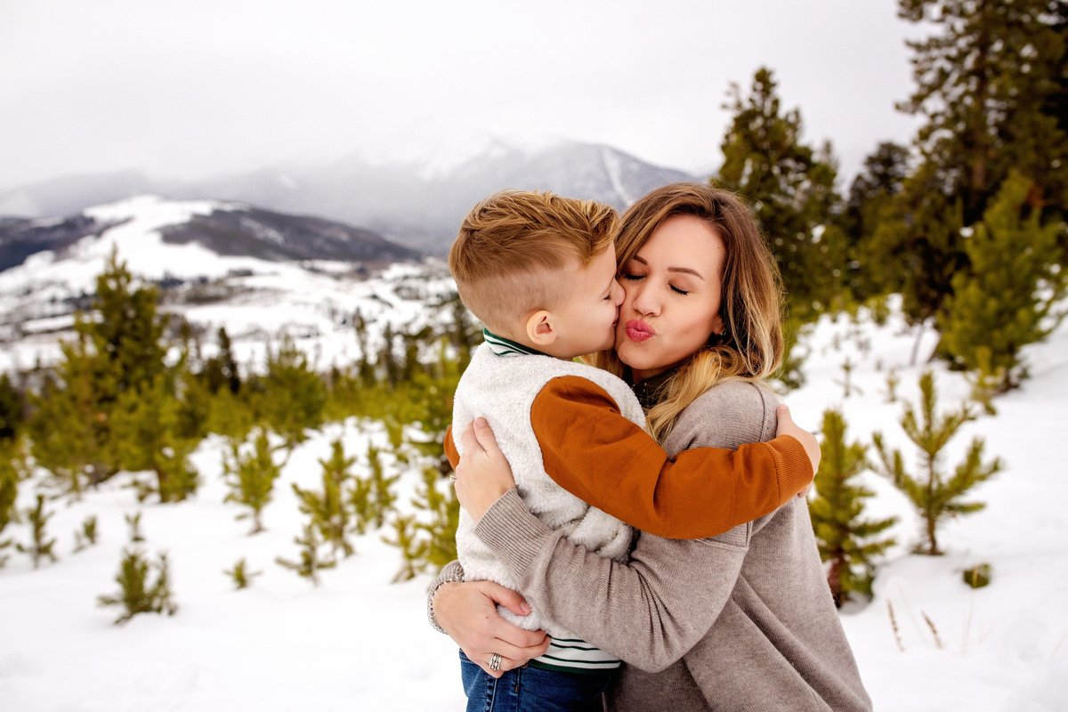 Mum giving a kiss to her son in the snowy Colorado mountains