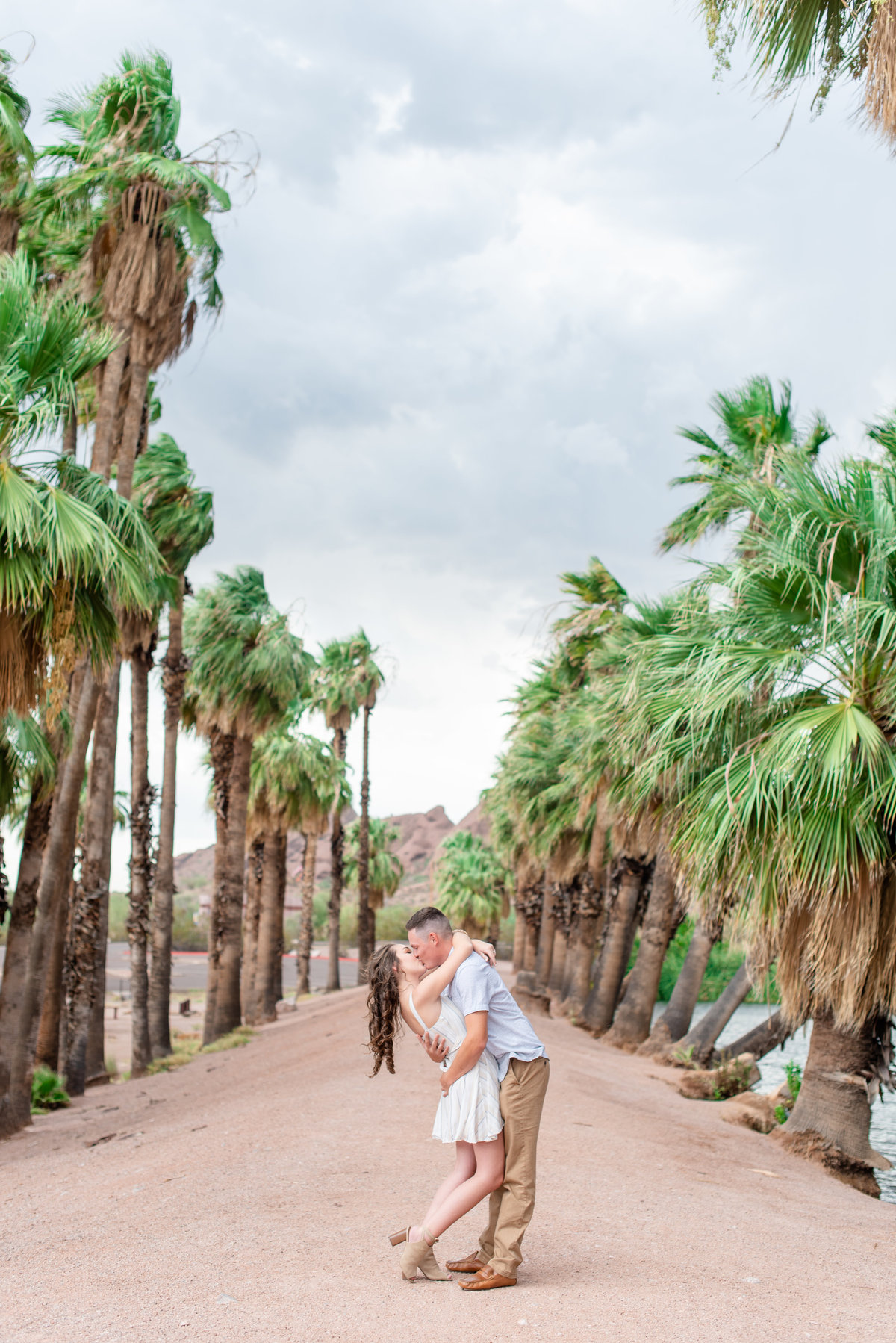 boy dips girl and kisses her in front of palm trees at papago park