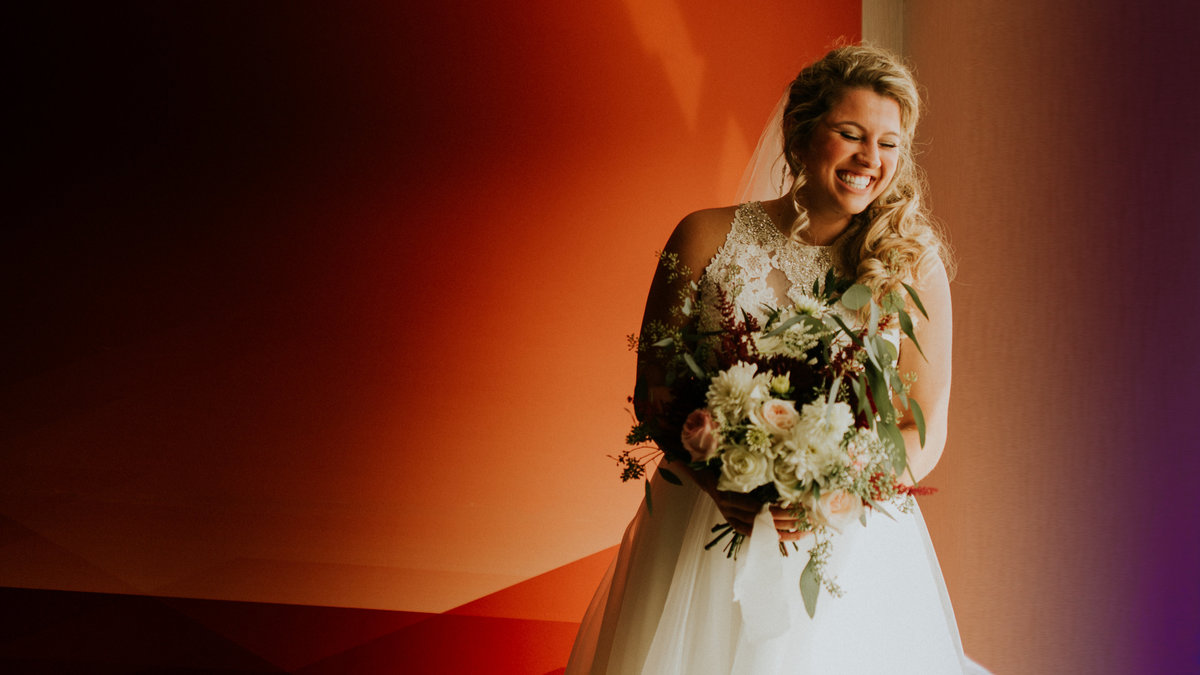 A portrait of the bride laughing in front of a bright orange wall